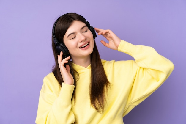 Menina jovem adolescente sobre parede roxa, ouvir música e cantar