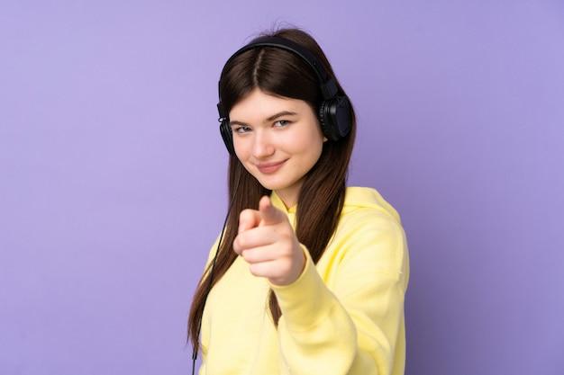 Menina jovem adolescente ucraniano sobre parede roxa, ouvindo música e apontando para a frente