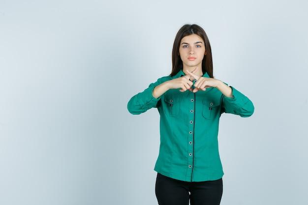 Menina jovem batendo os dedos indicadores, gesticulando o sinal x na blusa verde, calça preta e parecendo feliz. vista frontal.