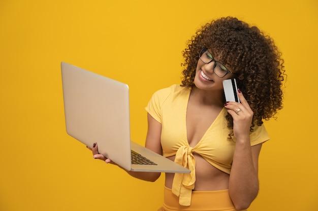 Menina jovem bonita de cabelos cacheados com laptop e cartão de crédito