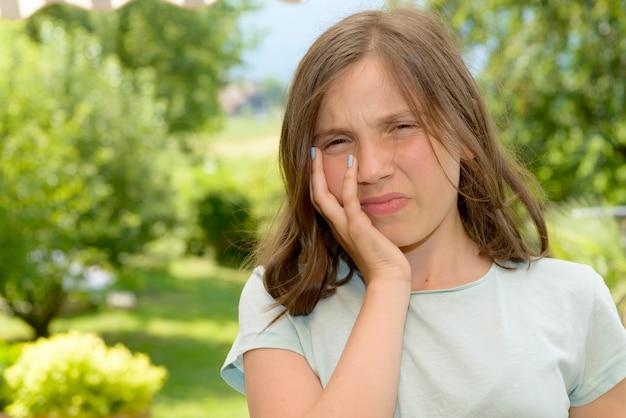Menina jovem bonito criança tem uma dor de dente