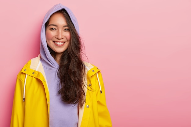 Menina jovem com cabelo escuro, usa um casaco roxo com capuz, veste uma capa de chuva amarela e sorri agradavelmente