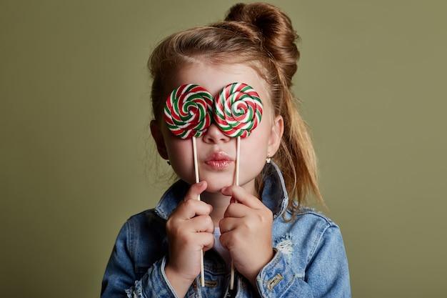 Menina jovem, comer, redondo, doce, licks, pirulito