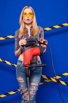 Menina jovem construtor de camisa quadriculada, jeans e óculos segurar broca
