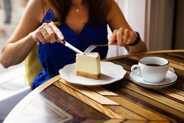 Menina jovem corta um pedaço de bolo de queijo com creme, no fundo de uma xícara de café, close-up.