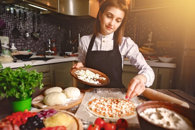 Menina jovem, cozinhando pizza