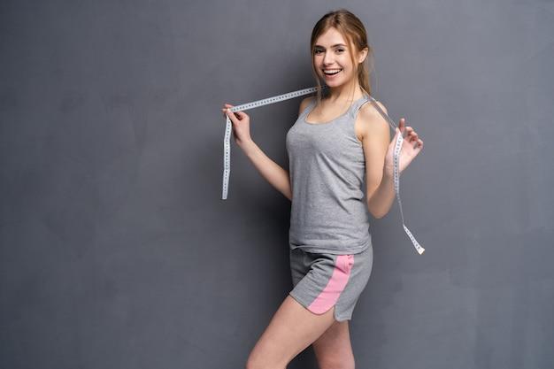 Menina jovem, desportiva, em forma e bonita com a fita métrica.