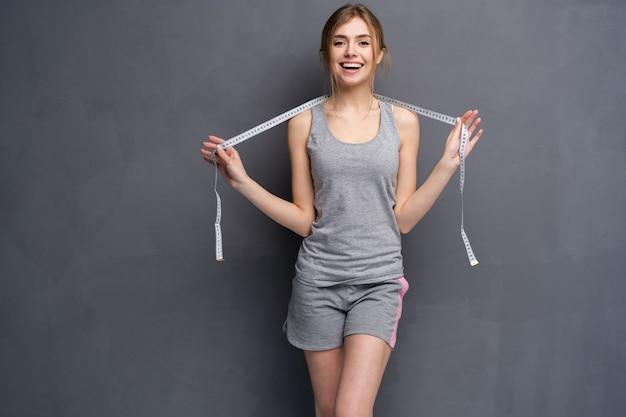 Menina jovem, desportiva, em forma e bonita com a fita métrica