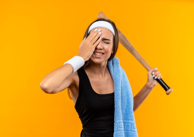 Menina jovem e bem desportiva dolorida com uma toalha no ombro, segurando o taco de beisebol, colocando a mão na cabeça, sofrendo de dor de cabeça com os olhos fechados, isolado na parede laranja