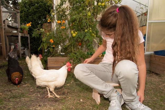 Menina jovem e bonita, alimentando a galinha na casa da fazenda