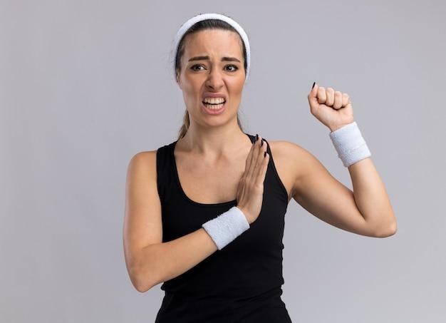 Menina jovem e bonita e esportiva irritada usando fita para a cabeça e pulseiras, olhando para o lado, o punho cerrado, mantendo a mão no ar