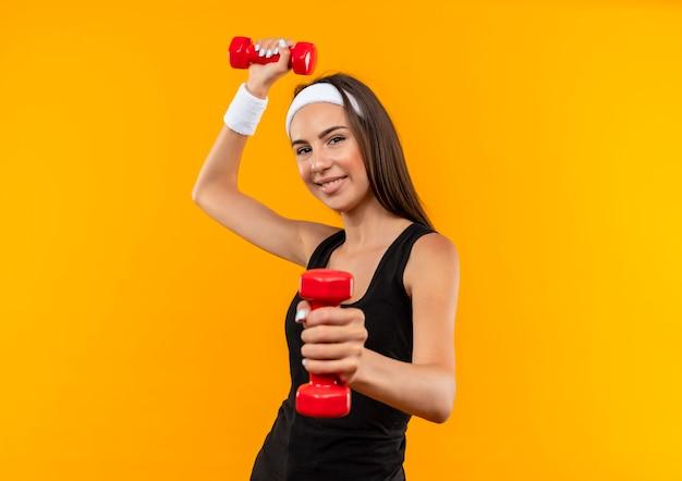 Menina jovem e bonita e esportiva satisfeita usando bandana e pulseira, esticando-se e levantando halteres isolados no espaço laranja