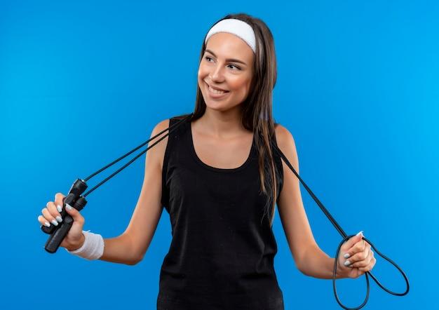 Menina jovem e bonita e esportiva satisfeita usando bandana e pulseira, segurando a corda de pular em volta do pescoço, olhando para o lado isolado no espaço azul