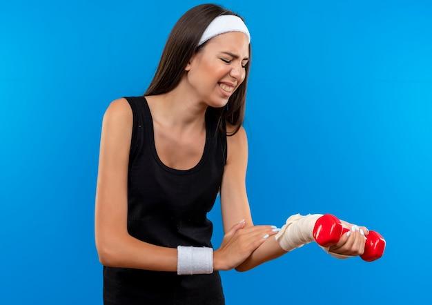 Menina jovem e bonita e esportiva usando bandagem e pulseira, segurando um haltere, colocando a mão e olhando para o pulso machucado envolto em uma bandagem isolada na parede azul