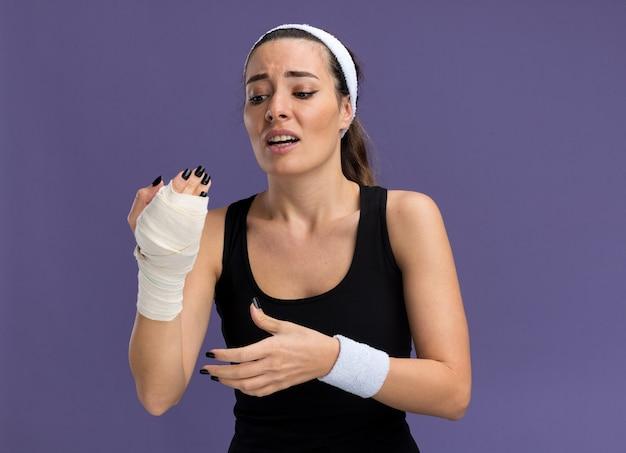 Menina jovem e bonita e esportiva, usando bandana e pulseiras, olhando para o pulso ferido envolto em bandagem, mantendo as mãos no ar isoladas na parede roxa com espaço de cópia
