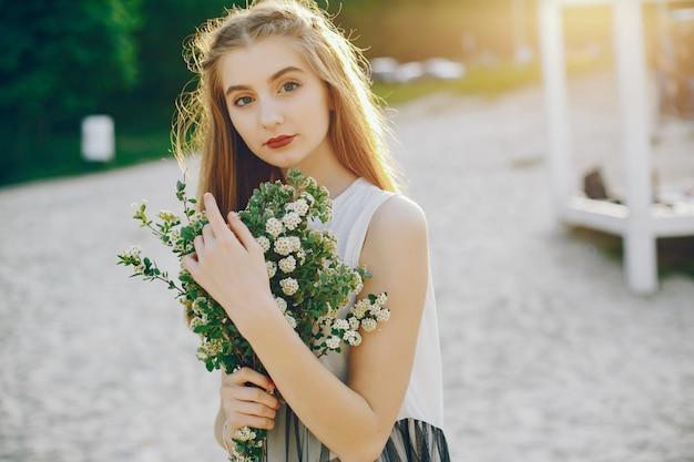 Menina jovem e bonita em um parque de verão