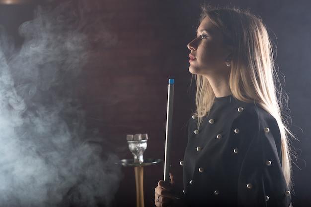 Menina jovem e bonita fuma um cachimbo de água