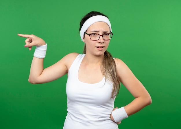 Menina jovem e desportiva insatisfeita com óculos ópticos, fita para a cabeça e pulseiras apontando para o lado