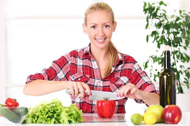 Menina jovem e feliz preparando comida saudável