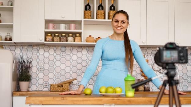 Menina jovem e saudável satisfeita gravando seu episódio de blog de vídeo sobre comida saudável em pé na cozinha em casa. mulher é simpática e sorridente