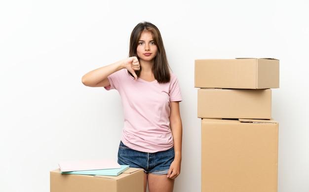 Menina jovem, em movimento, em, repouso novo, entre, caixas, mostrando, polegar baixo, sinal