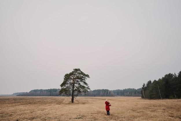 Menina jovem, em, um, casaco vermelho, plataformas, com, seu, costas, sob, um, árvore solitária, em, um, campo,