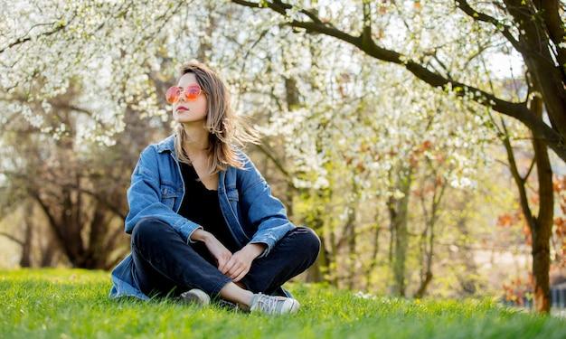 Menina jovem, em, um, jaqueta jeans, e, óculos de sol, sentando, perto, um, florescendo, árvore