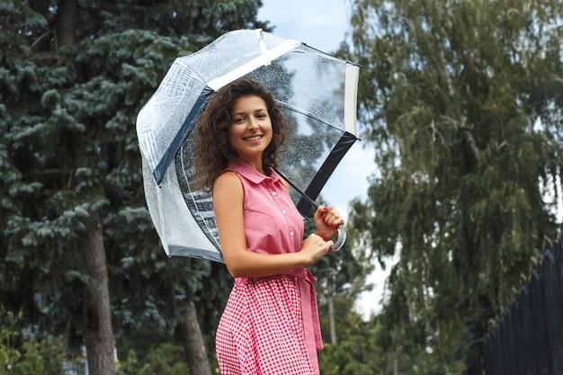 Menina jovem, em, um, vestido vermelho, com, um, guarda-chuva transparente, dançar, em, a, chuva, ficar, em, um, poça