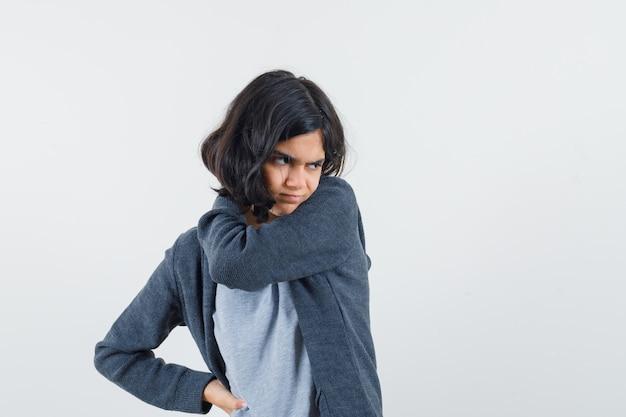 Menina jovem esticando uma mão enquanto segura algo e apontando para ela com o dedo indicador em uma camiseta cinza claro e um capuz cinza escuro com zíper na frente e parecendo exausta