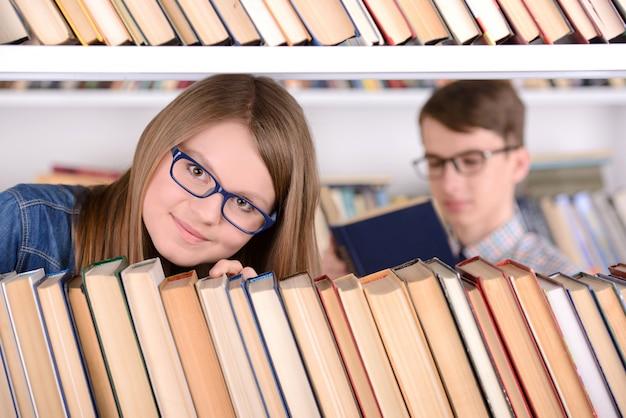 Menina jovem estudante com estante de seleção de livros