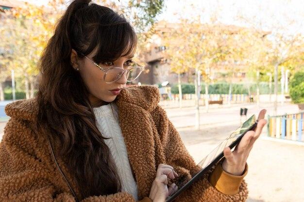 Menina jovem estudante de óculos trabalhando com seu tablet no parque.