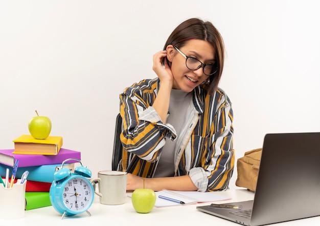Menina jovem estudante sorridente de óculos, sentada na mesa com ferramentas da universidade, olhando para o laptop e tocando a orelha dela, isolada na parede branca