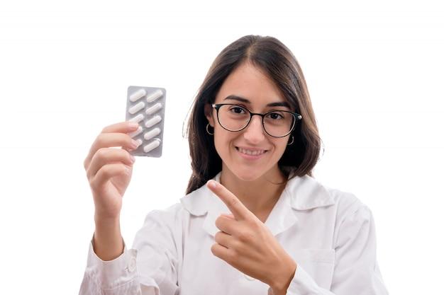 Menina jovem farmacêutico ou enfermeira com jaleco branco mostrando alguns comprimidos