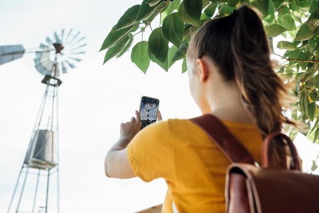 Menina jovem, fazendo exame um retrato, de, um, moinho de vento
