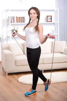Menina jovem, fazendo, exercícios, com, pular corda, casa