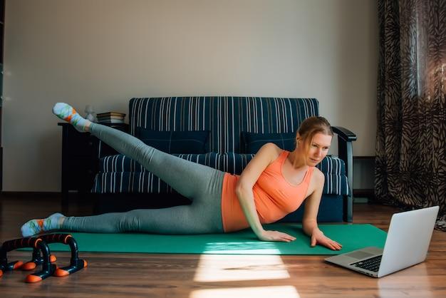 Menina jovem fazendo exercícios de fitness para as pernas com a ajuda de programas de treinamento on-line no laptop