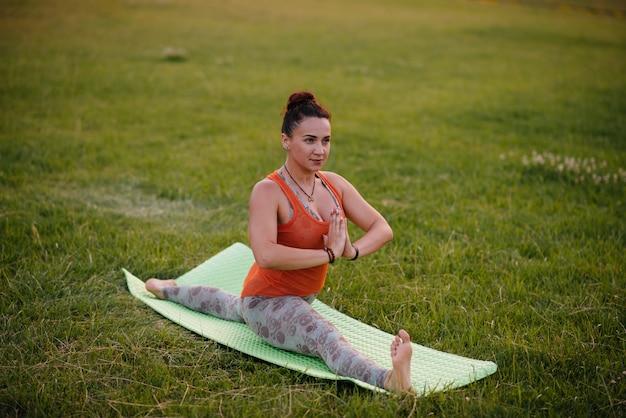 Menina jovem fazendo ioga ao ar livre, no parque durante o pôr do sol. estilo de vida saudável