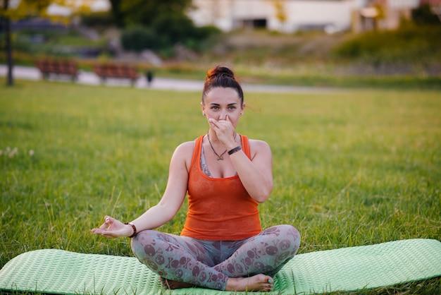Menina jovem fazendo ioga ao ar livre, no parque durante o pôr do sol. estilo de vida saudável.