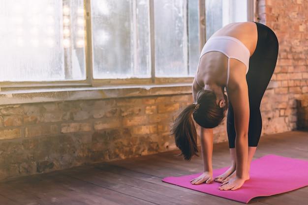 Menina jovem fazendo ioga sozinha na sala de ioga perto da janela