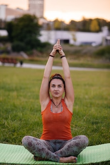 Menina jovem fazendo yoga ao ar livre, no parque durante o pôr do sol.