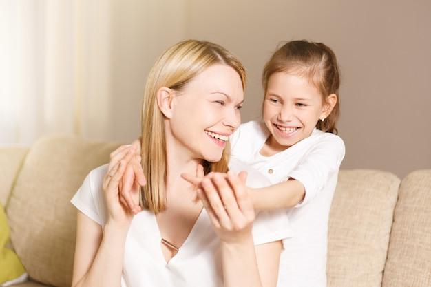 Menina jovem fechando os olhos da mãe, família e conceito de maternidade