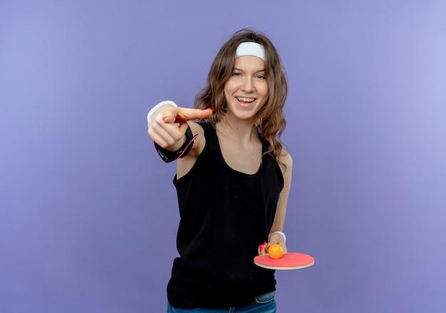 Menina jovem fitness em roupa esportiva preta com bandana segurando a raquete e as bolas de tênis de mesa apontando com o dedo indicador sorrindo em pé sobre a parede azul
