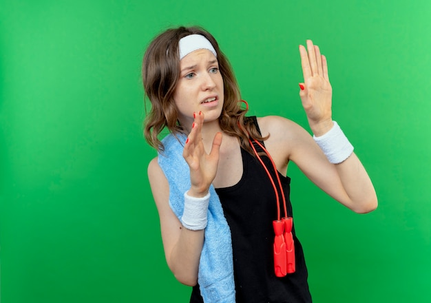 Menina jovem fitness em roupa esportiva preta com fita para a cabeça e toalha no ombro de mãos dadas, dizendo, não se aproxime com medo do verde
