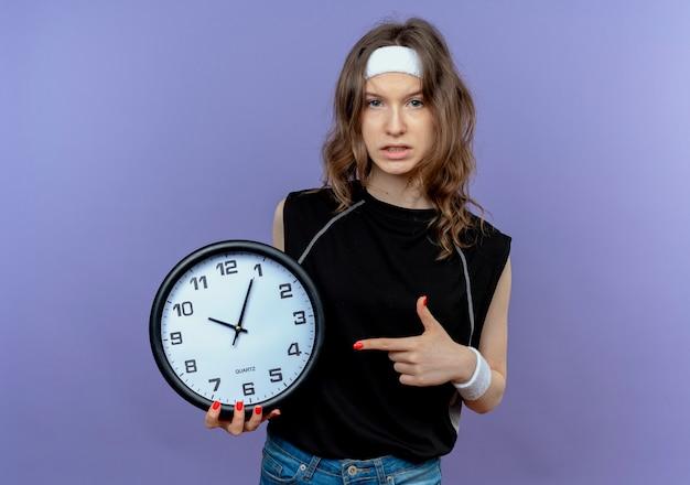Menina jovem fitness em roupa esportiva preta com fita para a cabeça segurando um relógio de parede apontando o dedo para ele com uma cara séria em pé sobre a parede azul