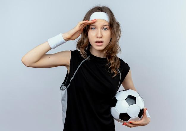 Menina jovem fitness em roupa esportiva preta com tiara segurando uma bola de futebol, olhando para longe com a mão na cabeça em pé sobre uma parede branca