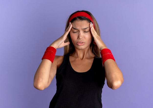 Menina jovem fitness em roupa esportiva preta e bandana vermelha, parecendo doente, tocando sua cabeça com as mãos, sofrendo de forte dor de cabeça, em pé sobre a parede azul