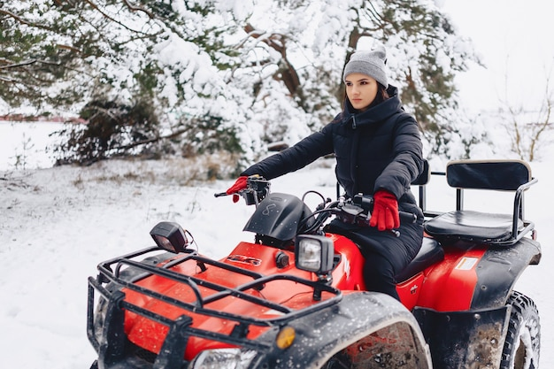 Menina jovem, ligado, um, motocicleta, passeios, em, neve-coberta, floresta pinho, em, inverno