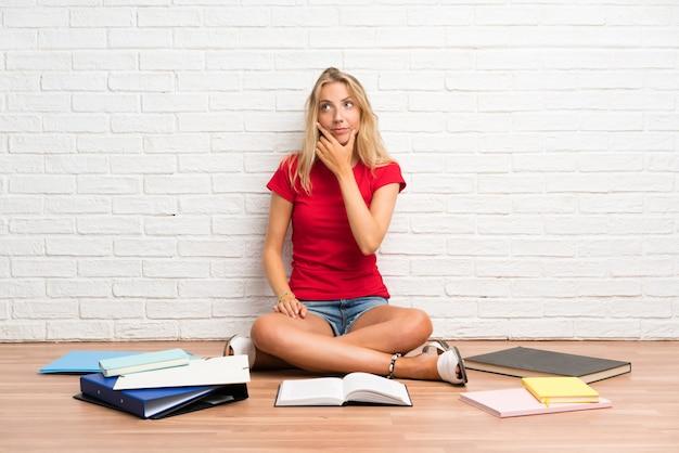 Menina jovem loira estudante com muitos livros no chão pensando uma idéia
