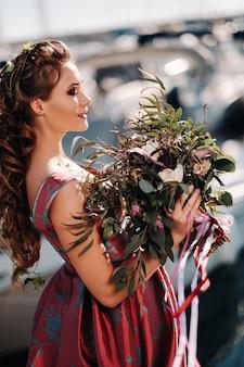 Menina jovem modelo em um lindo vestido com um buquê de flores na praia na frança. menina com flores na primavera, provença, na riviera francesa.
