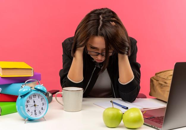 Menina jovem pensativa de óculos, sentada na mesa com as ferramentas da universidade, fazendo lição de casa, olhando para baixo e segurando a cabeça isolada na parede rosa